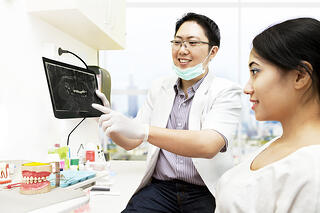 bigstock-Asian-Dentist-With-X-ray-And-P-36079342